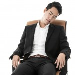 Young business man feel asleep, sitting in his office chair.
