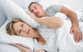 Annoyed woman with pillow over her ears next to snoring husband