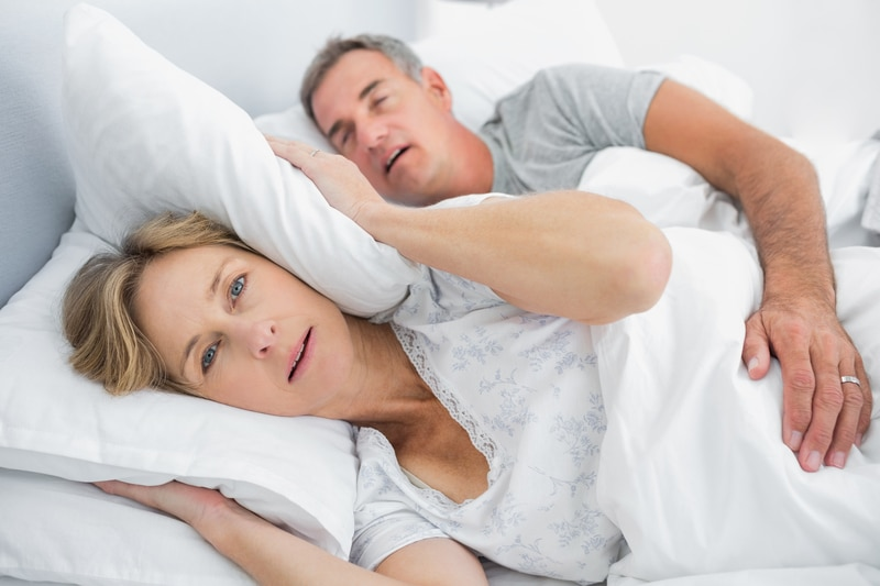 Middle aged couple in bed together, with the wife awake from her husband's snoring.