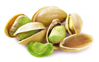 Close up of a handful of pistachios on a white background