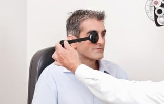 Middle aged man taking an eye exam at a doctor's office