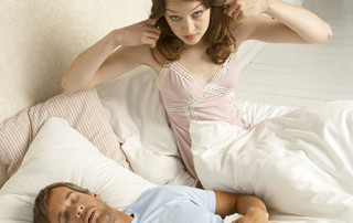 Woman annoyed by the sound of her husbands snoring