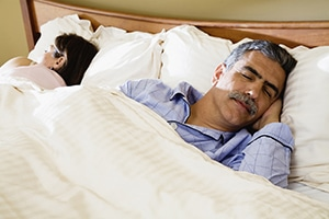 Middle-aged couple fast asleep in bed