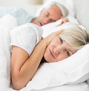 Woman awake and covering ears to ignore husband's snoring