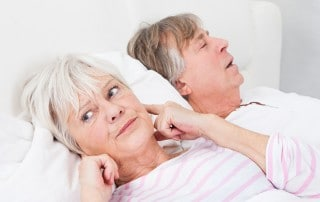 Senior woman annoyed by husbands snoring