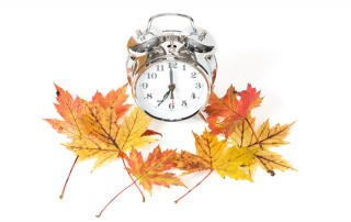 A clock with autumn leaves