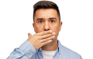 Man covering mouth due to bad breath
