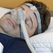 Man sleeping while wearing a CPAP mask.