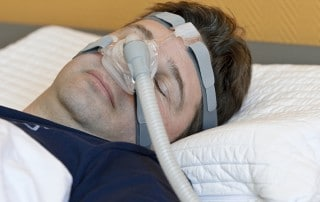 Man sleeping while wearing a CPAP mask.