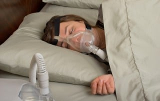 Woman lays on her side in bed with CPAP mask on