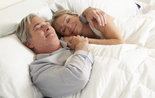 Older couple rests peacefully in bed together, snuggling