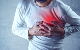 Man grasps at his chest while having a heart attack