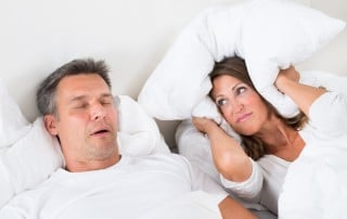 Couple lays in bed. The woman holds a pillow over her head while her husband snores