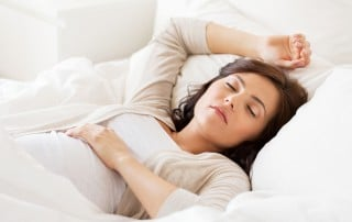 Woman takes a nap in bed with her right arm over her head