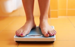 a woman with painted toenails stands on a weight scale in a yellow tiled bathroom