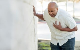 Older man leaning against a wall while having a heart attack