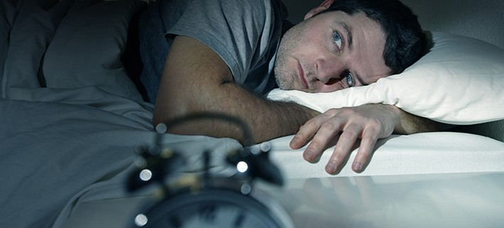 man in bed with eyes opened sufferin