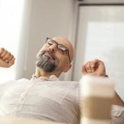 Portrait of senior businessman stretching office desk