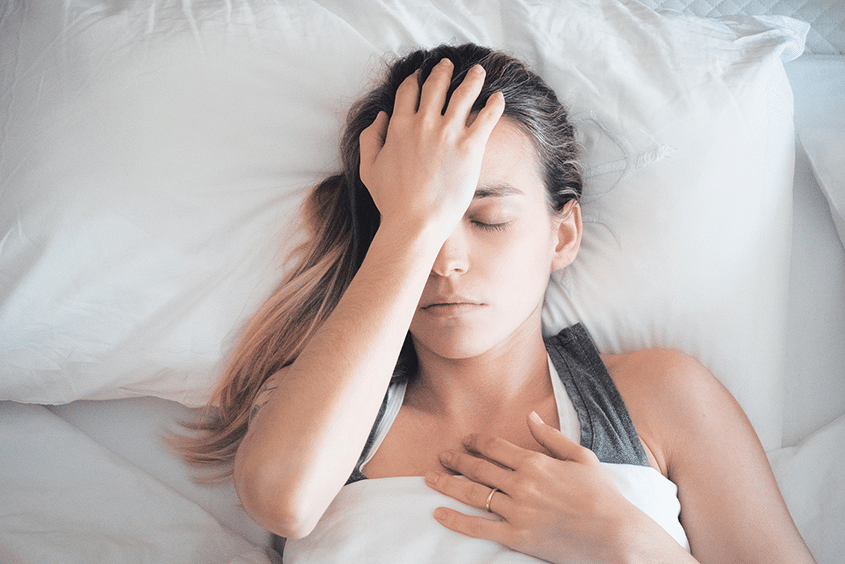Woman in bed with headache