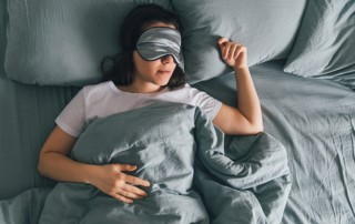 Woman resting peacefully with a sleep mask in bed with gray sheets