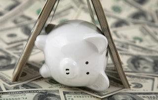 Piggy bank sleeping & snoring by some $100 bills