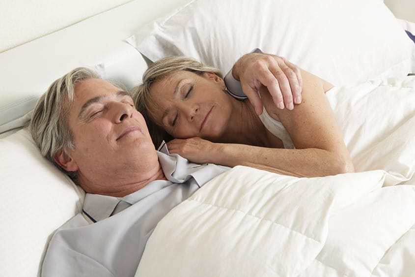 A happy middle aged couple rests peacefully in bed. Until recently they both couldn't sleep at night due to snoring. Luckily for them they found a solution.