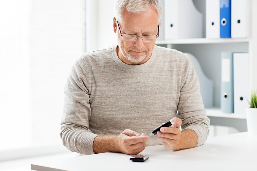 A Senior man with a glucometer checks his blood sugar buy pricking his finger. A recent study shows that treating sleep apnea can reduce the risk of Type 2 diabetes. Unfortunately, the study isn't all good news: it also highlights a major challenge in getting adequate sleep apnea treatment for people.
