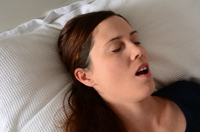 Beautiful female sleeping on bed at night while snoring and suffering from sleep apena. Research is one of many studies that suggest a link between sleep apnea and cancer risk.