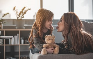 A young girl and her mother tease eachother by sticking out their tongues. Snoring doesn't just affect one person. When you're a snorer, it impacts the entire family. And it sometimes takes the entire family to come up with a good solution.