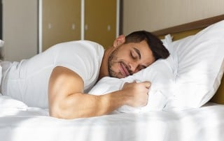 Young man sleeping peacefully in bed with a smile on his face