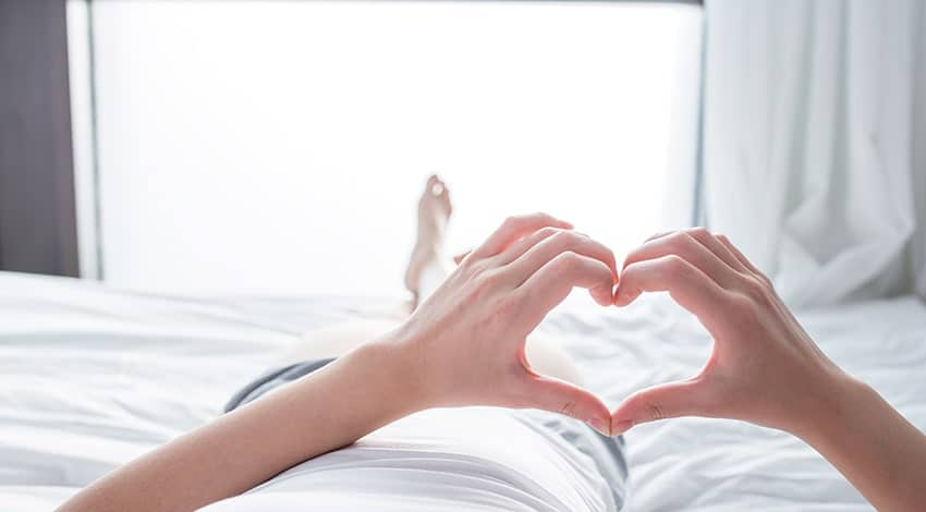 Hands in the shape of a heart are held up while a person relaxes in bed