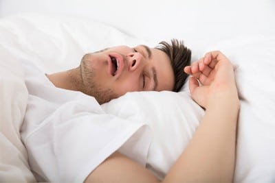 young man lays in bed with his mouth wide open, snoring