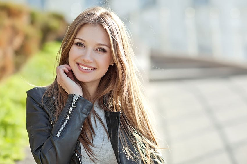 cute young woman brushes her hair back and smiles