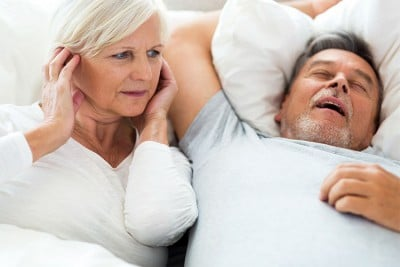woman plugging her ears next to a snoring husband