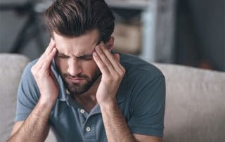 man suffering from a migraine headaches sits on couch