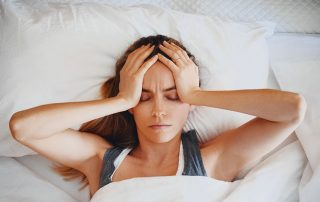 Woman in bed with a morning headache