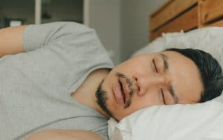 man laying in bed on his side, snoring.