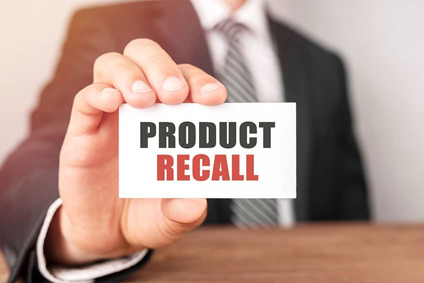 man holding a product recall card