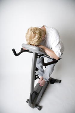 Woman falling asleep on exercise bike